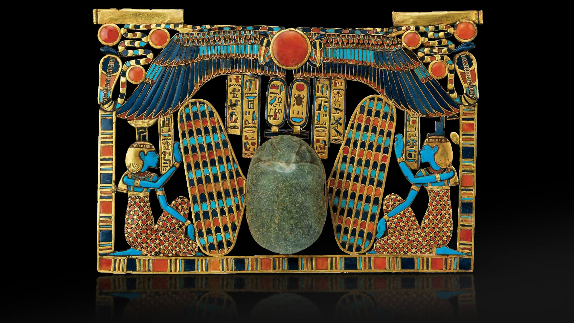 winged, large scarab beetle riding on a sacred barque and flanked by the goddesses Isis and Nephthys. The scarab serves a double function: as a heart scarab and as the ba of the sun god lighting the way to the Tutankhamun. Inlaid pectoral, scarab beetle with Isis and Nephthys. underworld.
